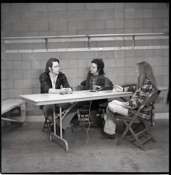 Bob Weir sitting at table with Mitch Sieser and Anne Baker (l. to r.), ca. March 28, 1973