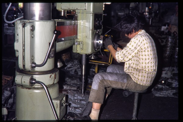 Shanghai tractor building factory: woman operating massive drillpress, June 1978