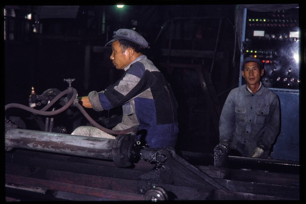 Shanghai tractor building factory: workers operating machines, June 1978
