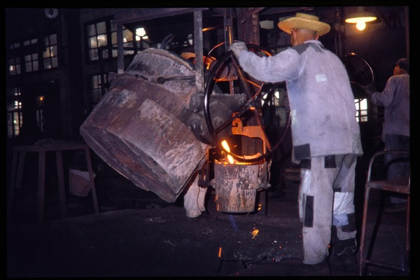 Shanghai tractor building factory: worker pouring iron into mould, June 1978