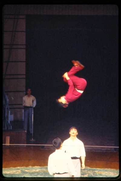Shanghai acrobats: acrobat doing a flip in the air, June 1978