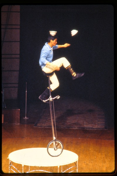 Shanghai acrobats: man balancing on tall unicycle, juggling dishes, June 1978
