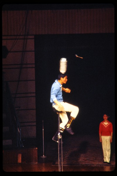 Shanghai acrobats: man on a tall unicycle balancing dishes on his head, June 1978