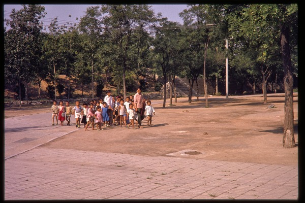 Group of children and teachers walking in park, June 1978