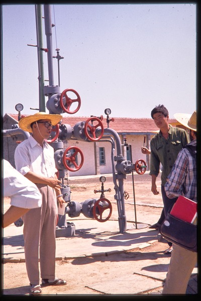 Man addressing group at oil field in front of wellhead pressure regulator, June 1978