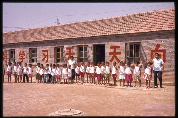 Children and teachers in schoolyard, probably a school for children of oil workers, June 1978
