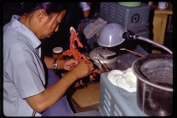 Arts and crafts factory: worker carving coral, June 1978