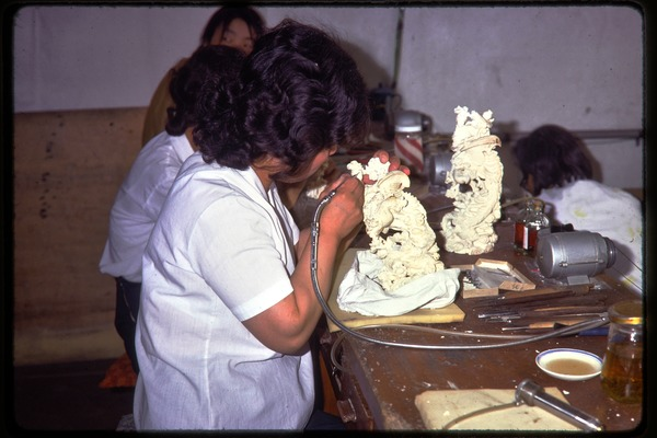 Arts and crafts factory: worker carving ivory, June 1978