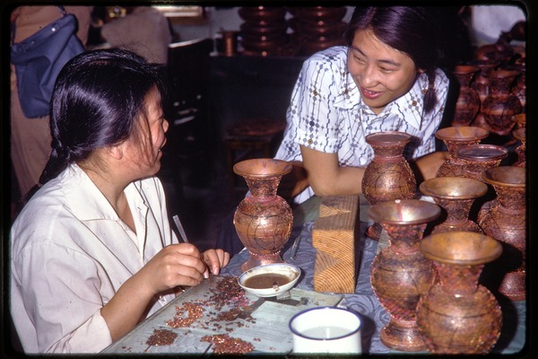 Arts and crafts factory: woman decorating vases, June 1978