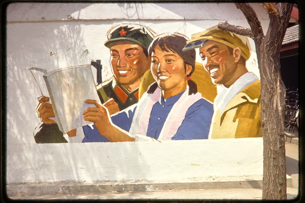 Outdoor poster of smiling soldier and workers reading, June 1978