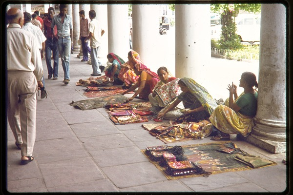 Women selling cloth bags and good alongside an open air walkway, ca. July 1978