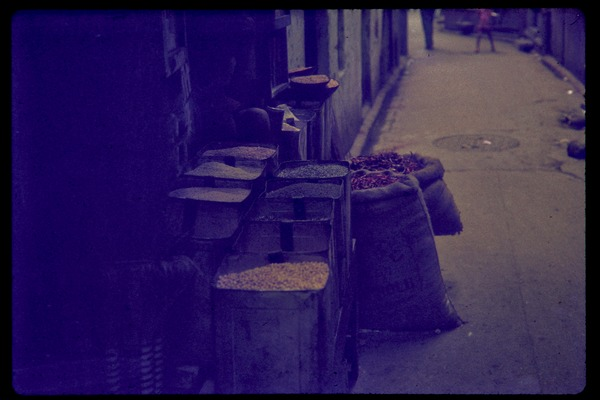 Bags of peppers and produce stashed in an alley, ca. July 1978