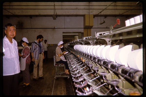 Cotton mill: operator at a spinning machine, June 1978