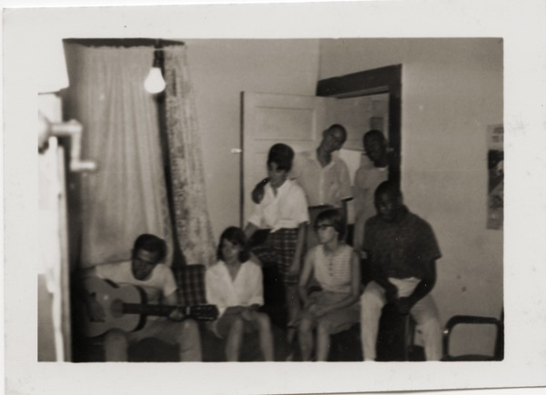 Civil rights workers inside Freedom House, including Gloria Xifaras Clark             (standing left), Kathy Dahl (seated, 2d from the right), and U.Z. Nunnally (seated far right), ca. 1965