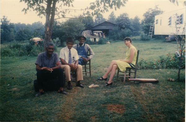 Charlie Hill, two unidentified men, and Marjorie Merrill (l. to r.) seated on a             lawn, ca. 1965