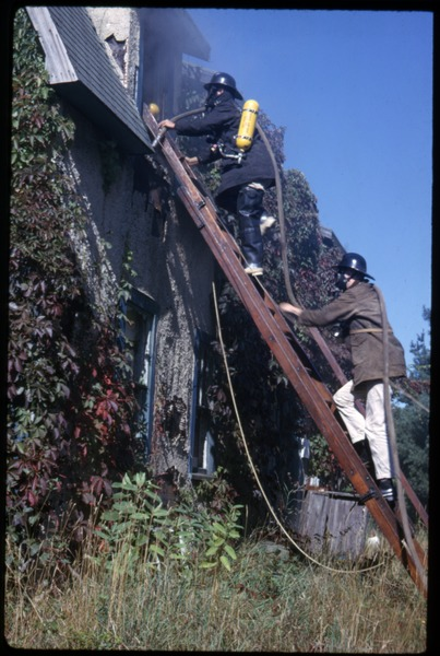 Preparing to burn Sam's house, Duxbury Cranberry Company: Fire fighters climbing a ladder to the second floor: , 1963