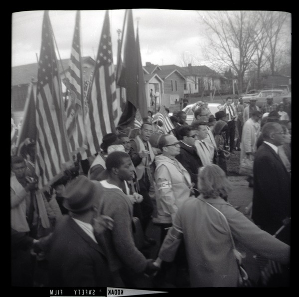 Marchers under a battery of American flags, ca. March 25, 1965