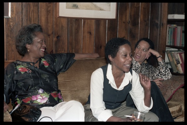 Johnnetta Cole, Esther Terry, and unidentified woman (r. to l.) seated on a             couch,at the book party for Robert H. Abel, November 1985