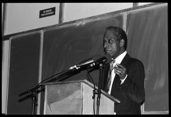James Baldwin lecturing at UMass Amherst: Baldwin standing at a podium with microphones: , 1984