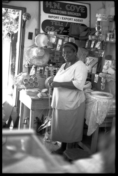 Woman plaiting palm leaf baskets in her store, Belize City, 1993