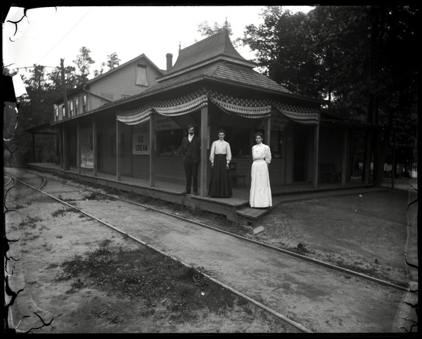 Rail station with ice cream parlor and restaurant, Lake Pleasant: A man and two women posed in front of the ice cream parlor and trolley tracks: , ca. 1900