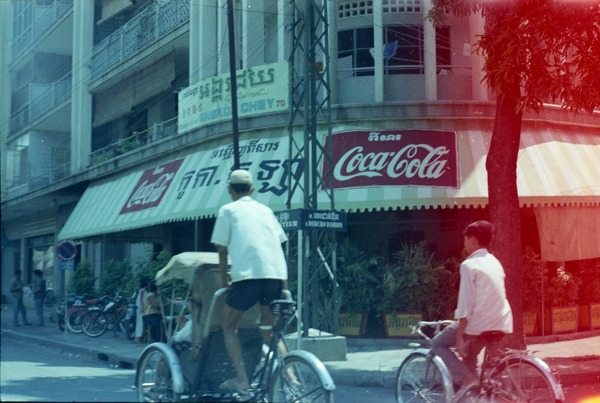 Cafe in downtown, with pedicap and boy on bicycle outside, May 1968