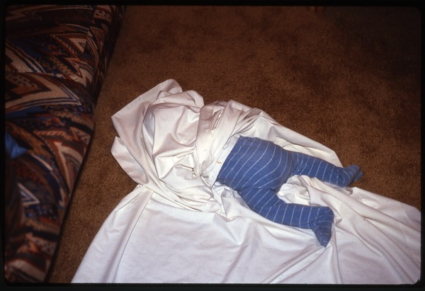 Baby lying on floor wrapped in sheet, February 1991