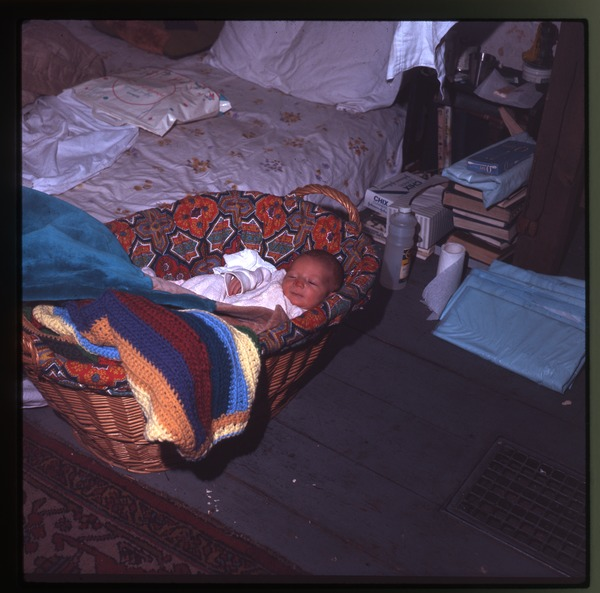 Baby (Eben) nestled in a basket, Montague Farm Commune, January 1971
