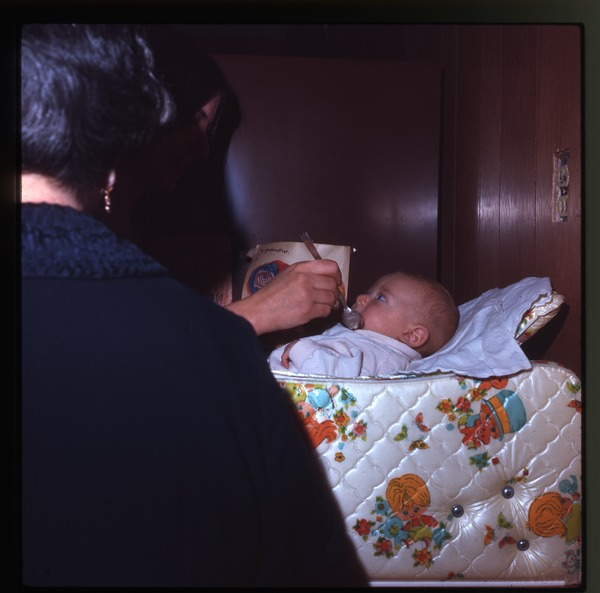 Nina Keller spoon feeding baby Eben, Montague Farm Commune, April 1971