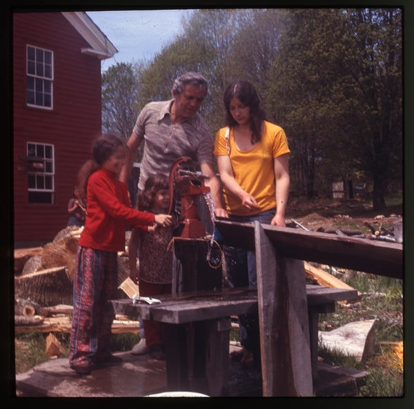 Nina Keller (right) and her father with two young girls at the water pump,
