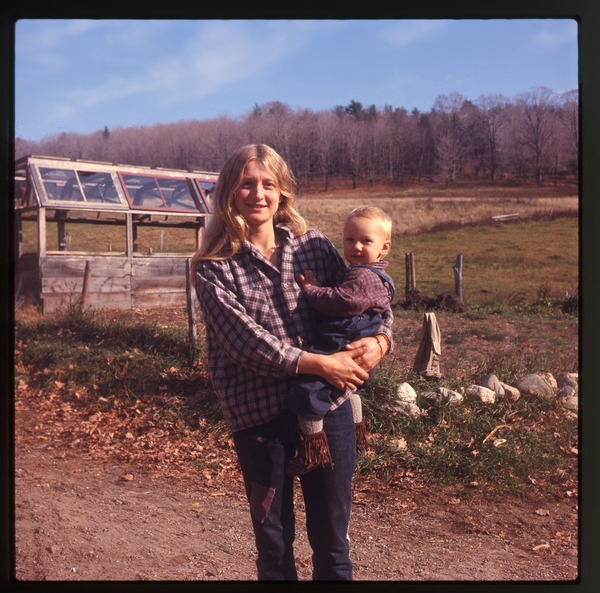 Janice Frey and baby Sequoya in front of a greenhouse, Montague Farm Commune, June 1972