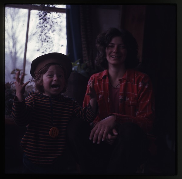 Nina Keller and young child (Eben?), inside house at Montague Farm Commune, March 1975