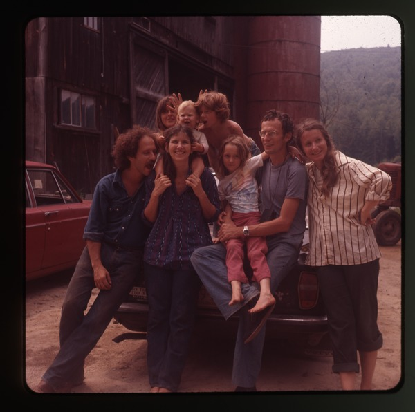 Montague farmers seated on the rear of car outside the barn, Montague Farm             Commune, June 1978