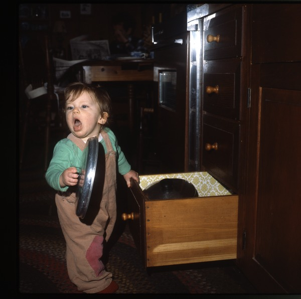 Baby with pans, Wendell Farm, March 1979