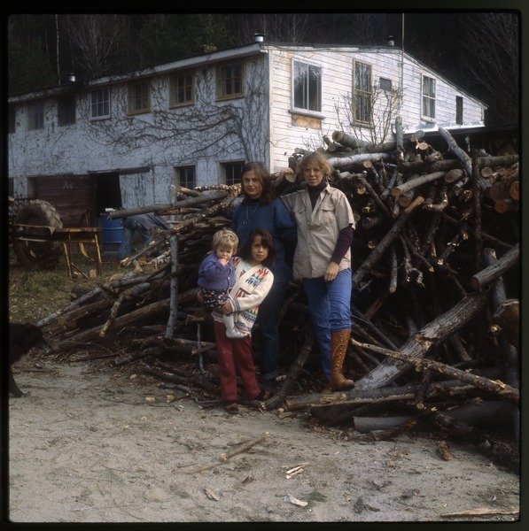Unidentified people posed on woodpile, Wendell Farm, November 1979