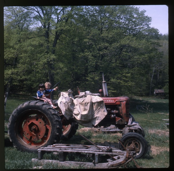Two kids on tractor, Wendell Farm, May 1982
