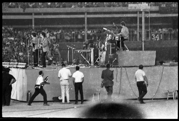 Beatles concert at Shea Stadium: Beatles in performance on stage: George             Harrison and John Lennon up front, Ringo Starr on drums (l. to r.), August 15, 1965
