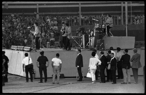 Beatles concert at Shea Stadium: Beatles on stage in performance: Paul McCartney             at microphone, George Harrison and John Lennon on guitars, Ringo Starr on drums (l. to r.), August 15, 1965