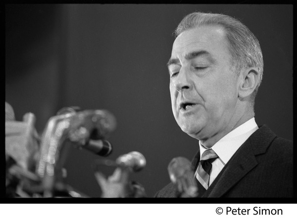 Presidential candidate Eugene McCarthy behind a bank of microphones, giving a speech at Boston University, April 10, 1968