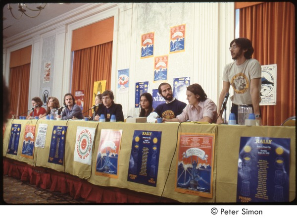 MUSE concert and rally: Press conference, Harvey Wasserman standing with (l-r) Sam Lovejoy, John Hall, Winona LaDuke, Graham Nash, James Taylor, Bonnie Raitt, and an unidentified woman, September 1979