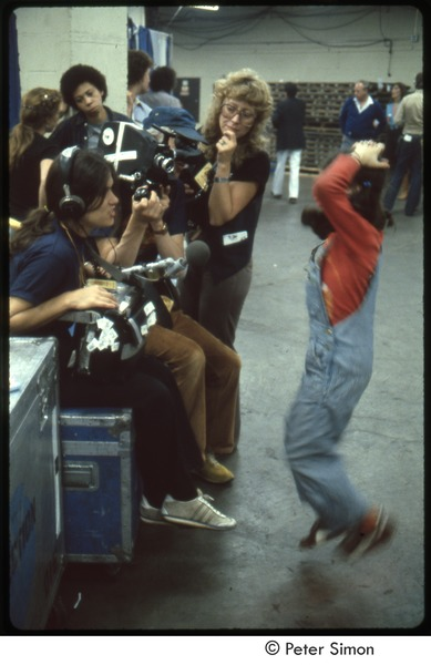MUSE concert and rally: young girl jumping while being filmed backstage at the MUSE concert, September 1979