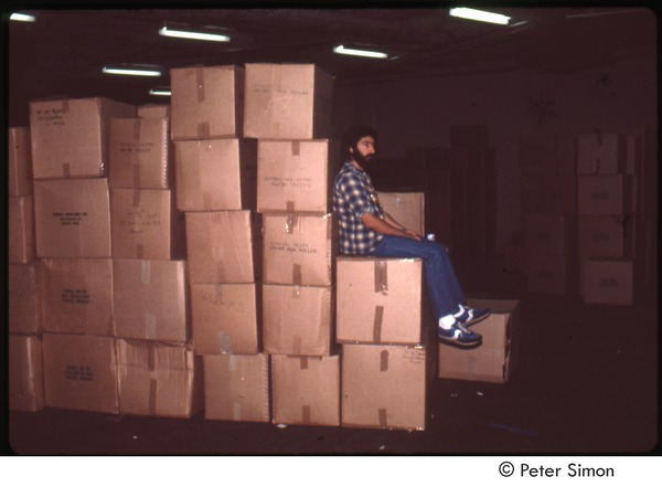MUSE concert and rally: man sitting on stack of boxes backstage at the MUSE concert, September 1979