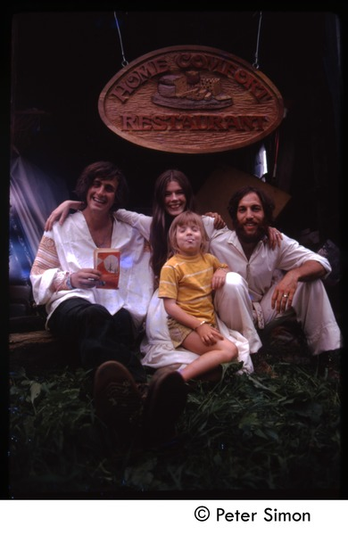 TIm Rossner(?), Catherine Blinder, Elliot Blinder and child (l. to r.) seated under sign for             Home Comfort Restaurant, Tree Frog Farm commune, August 1972