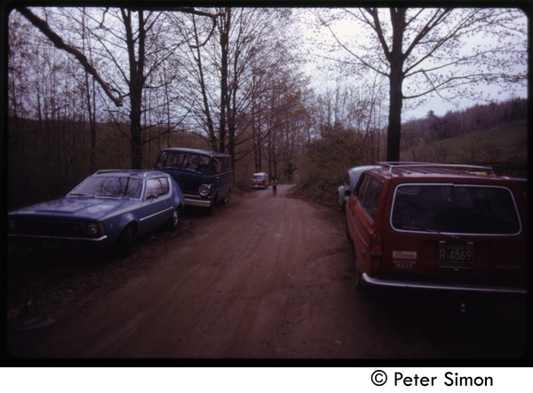 Cars parked along a dirt road, Tree Frog Farm commune, May 1973