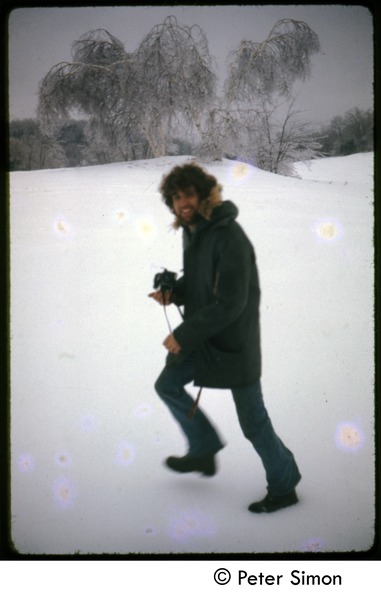 Peter Simon with camera, trudging through the snow after an ice storm, Tree Frog Farm Commune, April 1973