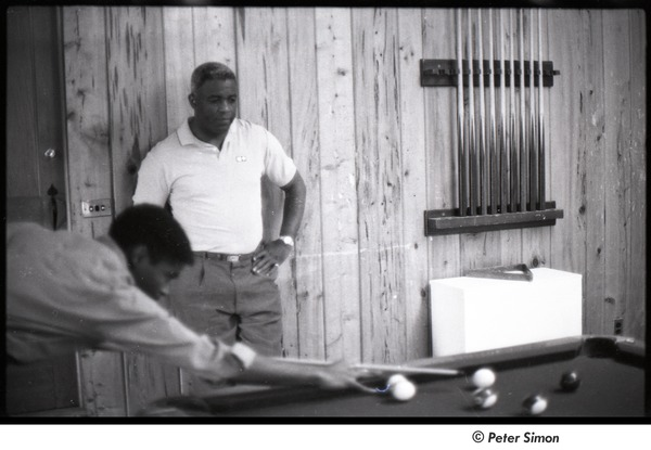 Party at Jackie Robinson's house: man playing pool while Jackie Robinson watches, December 22, 1963