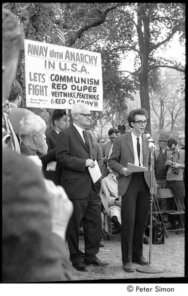 Resistance rally: speaker on Boston Common, counter protester holding sign in background, October 16, 1967