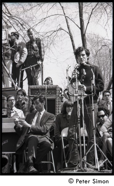 Resistance on the Boston Common: Terry Cannon (draft resister and member of the             Oakland 7) addressing the crowd, Howard Zinn  checking his notes on stage (far left), April 3, 1968