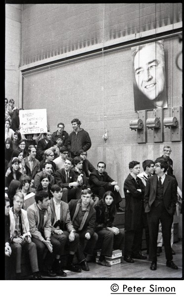 Audience awaiting speech by presidential candidate Eugene McCarthy at Boston             University, standing under large poster for McCarthy, April 10, 1968
