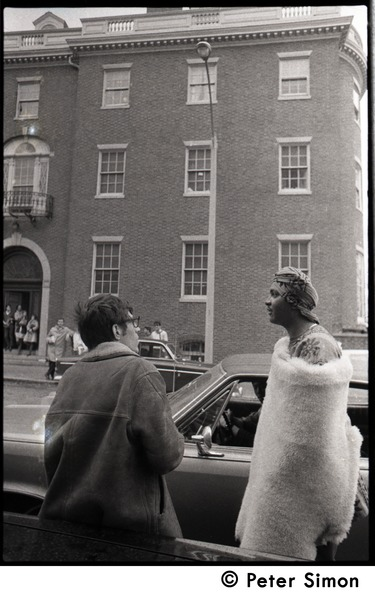 Umoja (Black student union) activist standing by car, wrapped in a sheepskin and talking to a white             onlooker, at site of occupied administration building, Boston University, April 25, 1968